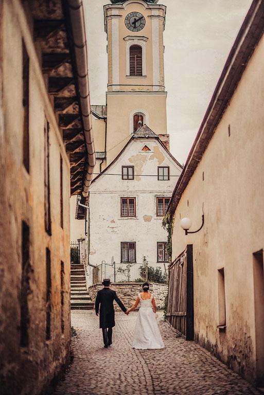 Nevěsta s ženichem jdou zády uličkou ke kostelu v Poličce