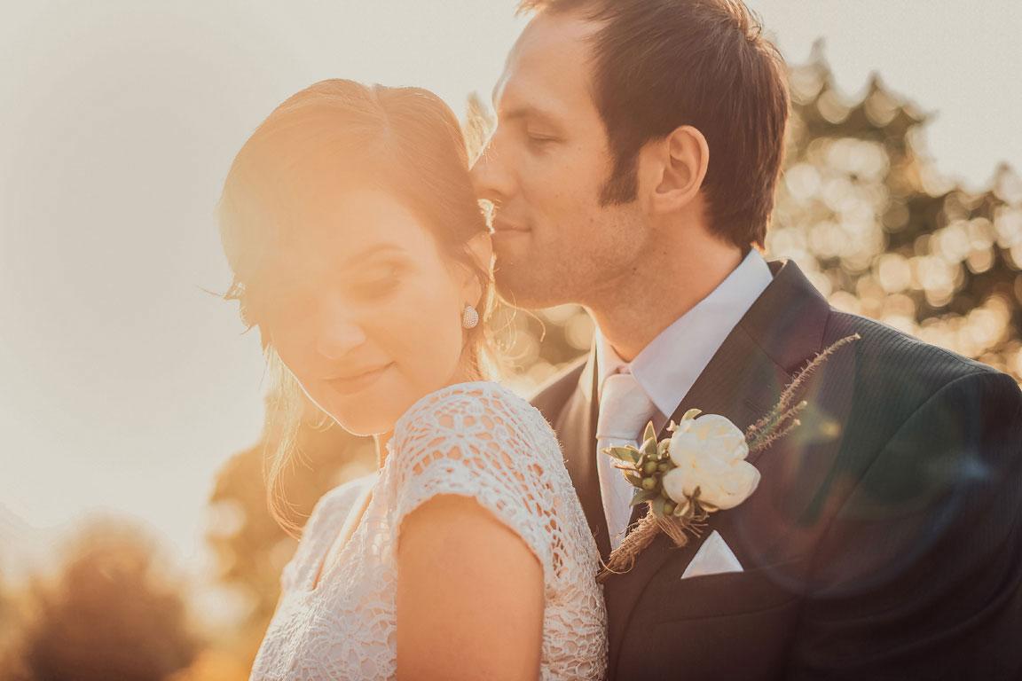 v protisvětle při západu slunce se ženich dotýká nosem vlasů nevěsty, která má zavřené oči