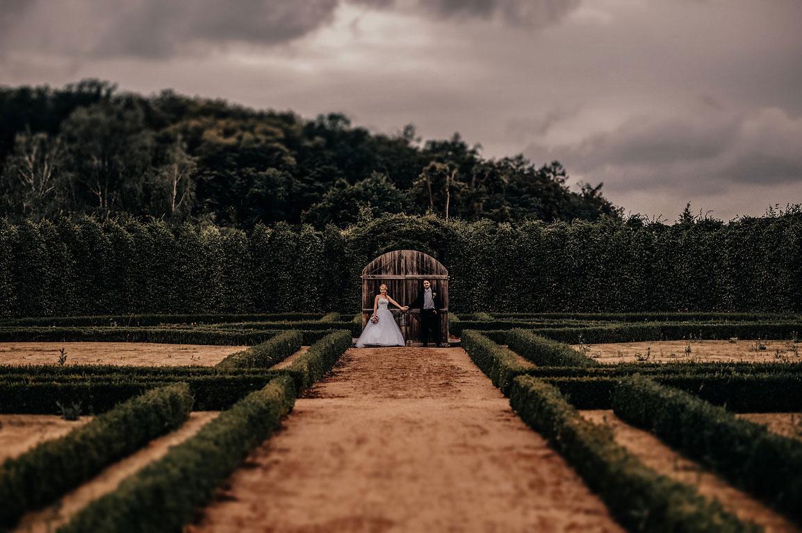 ženich s nevěstou stojí opření o bránu a drží se za ruce v areálu zámecké zahrady zámku Štáblovice