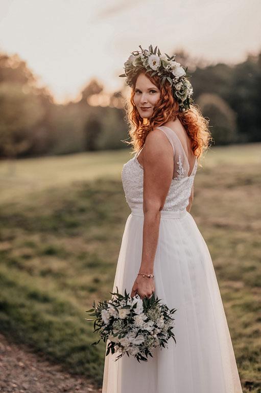 Boho nevěsta s květinovým věnečkem a kytkou v ruce s ohlíží za sebe