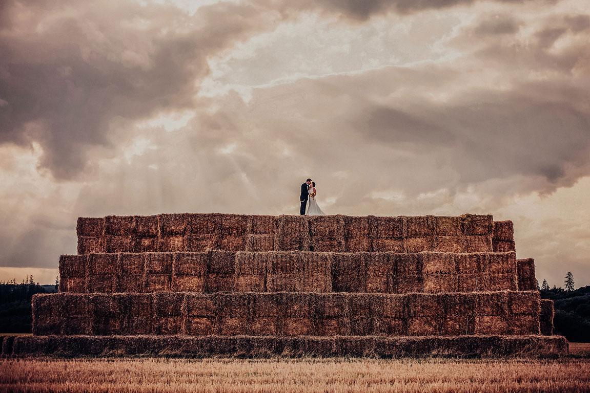 ženich se nevěstou se líbají v objetí na velké kopě složené z kostek slámy