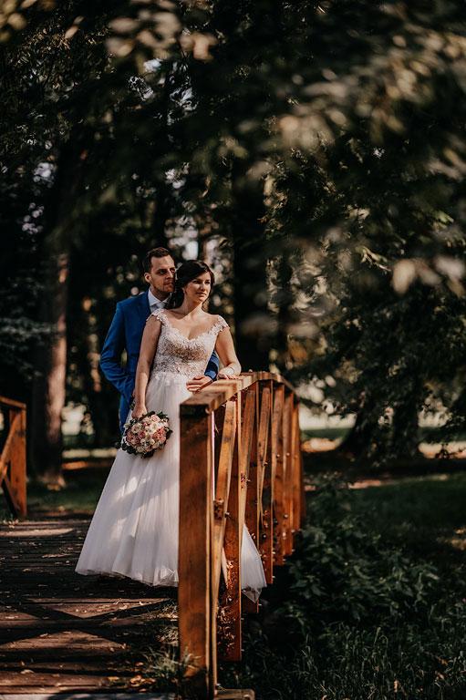 Ženich s nevěstou stojí u zábradlí mostu v Zámeckém parku Kravaře