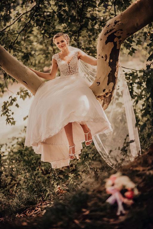Nevěsta sedí na prohnuté větvi stromu a v popředí leží svatební kytice