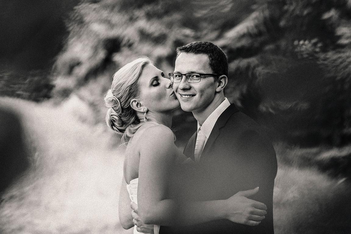 Černobílá fotografie nevěsty dávajícé pusu na líčko ženicha koukajícího do kamery