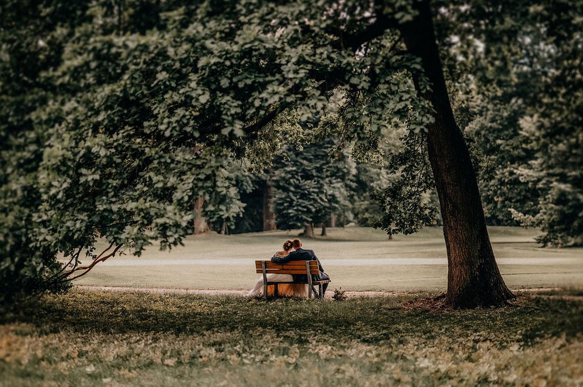 Pohled zezadu na sedícího ženicha s nevěstou na lavičce v Zámeckém parku kravaře