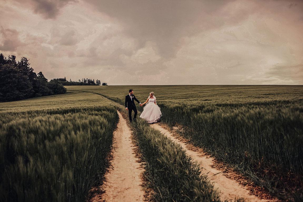 ženich s nevěstou jdou za ruce vyšlapanou cestičkou v poli s obilím a koukají na sebe