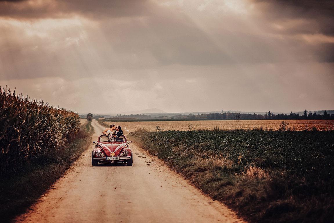 ženich se nevěstou se líbají v kabrioletu VW brouk stojícím na zpevněné cestě u pole s kukuřicí