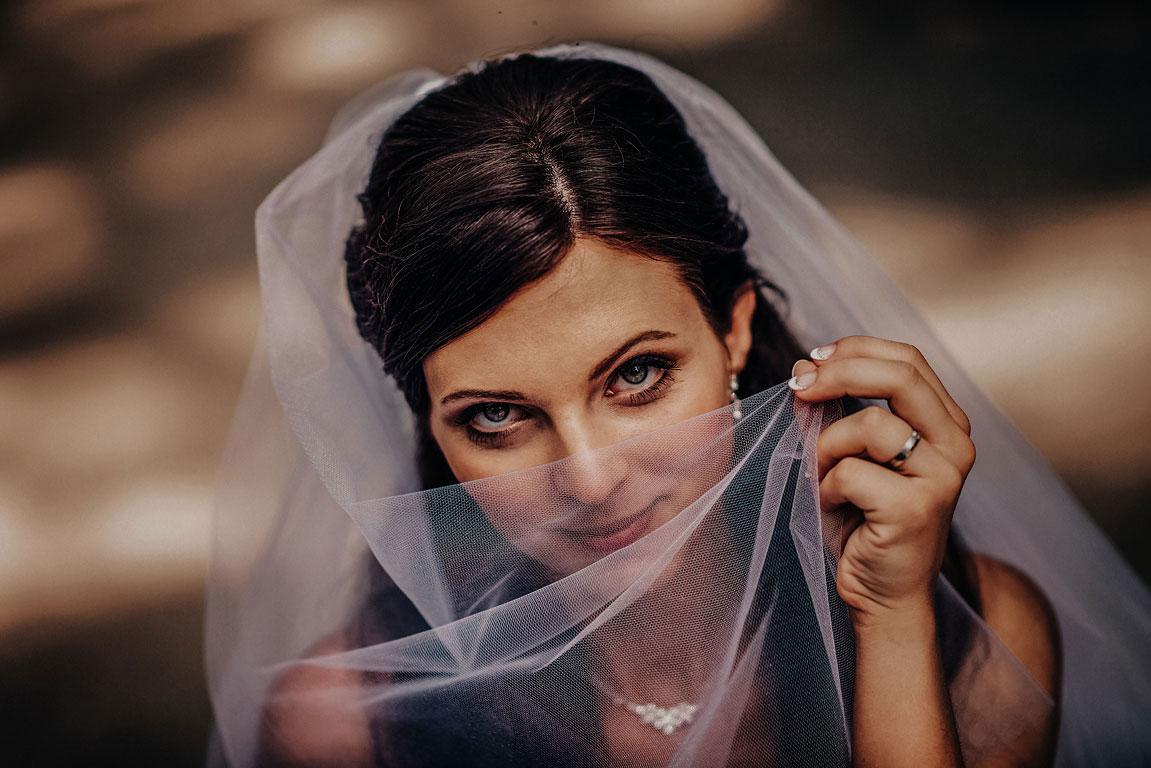 Nevěsta si zakrývá nos ústa svatebním závojem