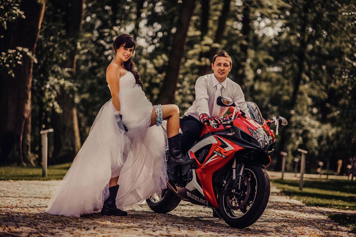 Ženich s nevěstou pózují u jejich motorky Suzuki. Nevěsta má vyhrnuté šaty a ukazuje podvazek.
