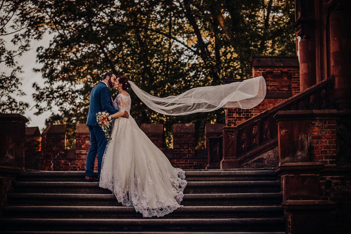 ženich s nevěstou se líbají na schodech u kaple v Hradci nad Moravicí. Nevěstě vlaje závoj.
