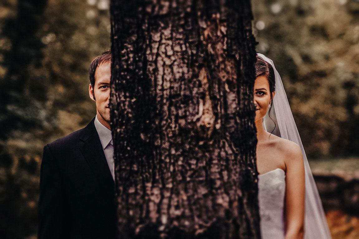 Nevěsta se ženich se schovávají za kmenem stromu. Každému jde vidět jen polovina obličeje.