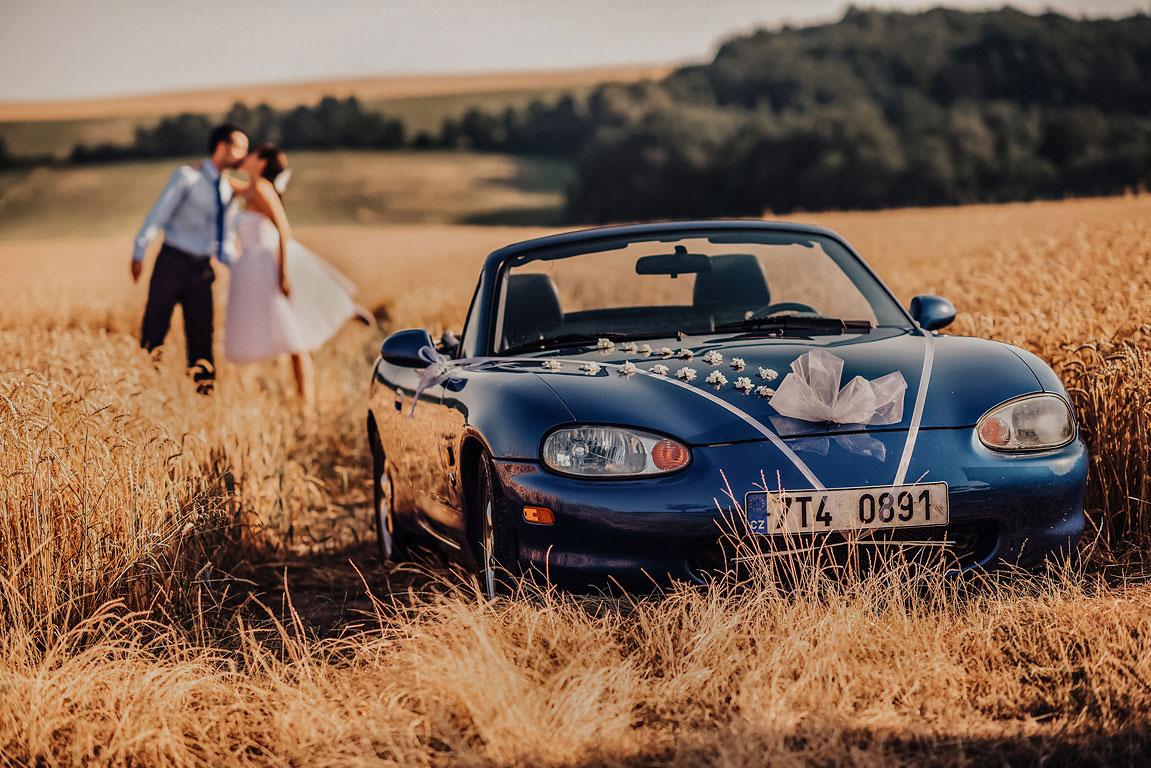 Pohled na Mazdu MX-5 svatebně vyzdobenou a v pozadí se líbající ženich s nevěstou.