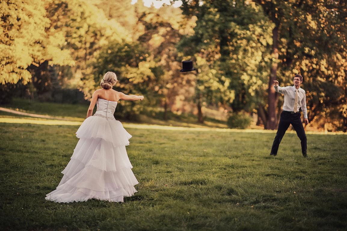 ženich s nevěstou si v parku v Raduni házejí cilindrem