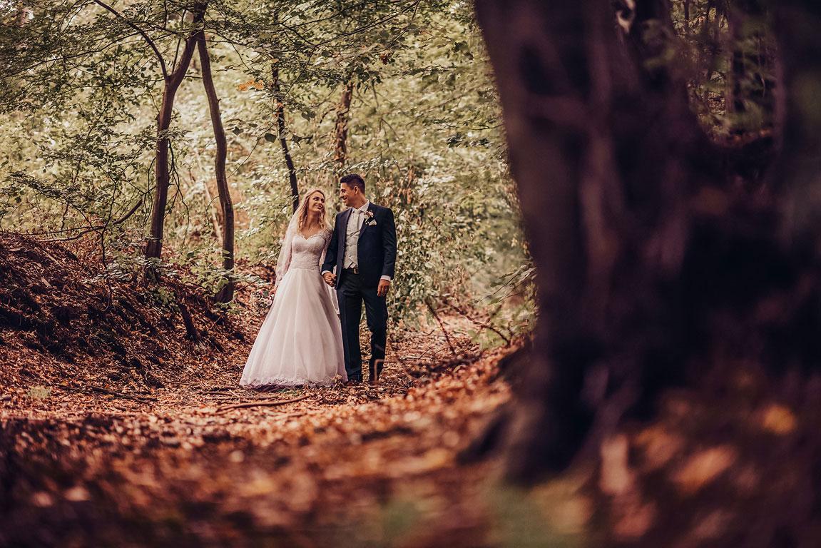 ženich a nevěsta se prochází podzimním lesem ve spadaném listí