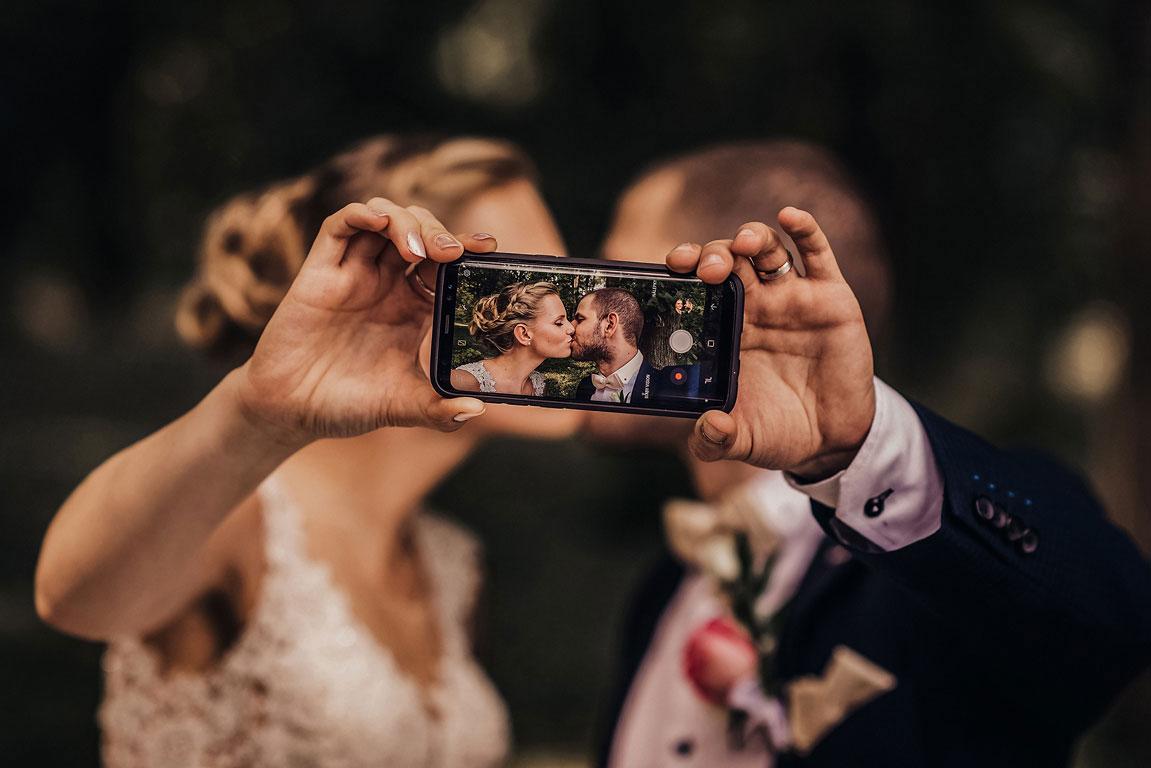 Ženich s nevěstou se líbají a před sebou drží mobil, kterým si dělají si selfie