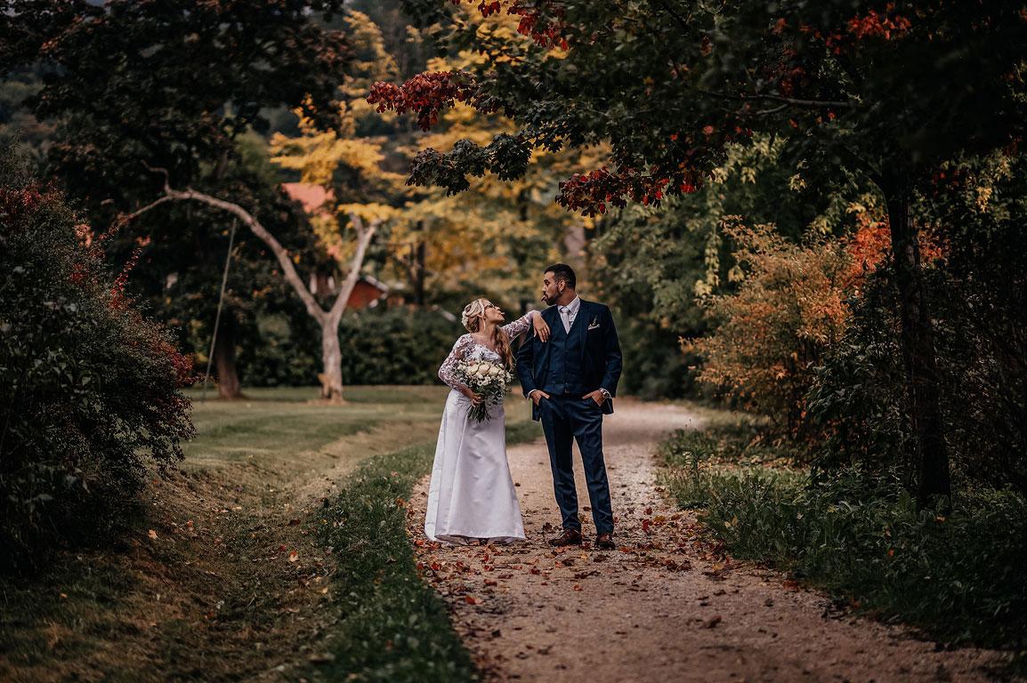 Ženich s nevěstou stojí na cestičce v podzimním parku a vyplazují na sebe laškovně jazyky
