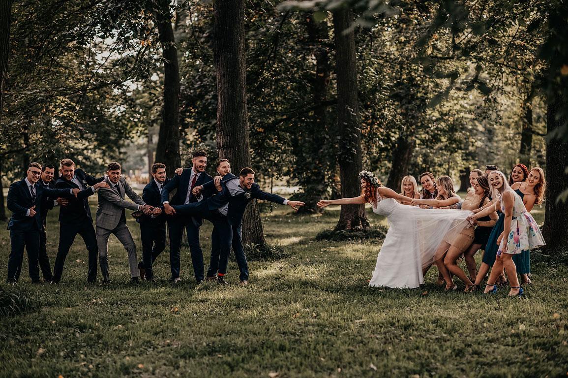 ženicha i nevěstu od sebe táhnou jejich přátelé a ti se snaží chytit za ruce