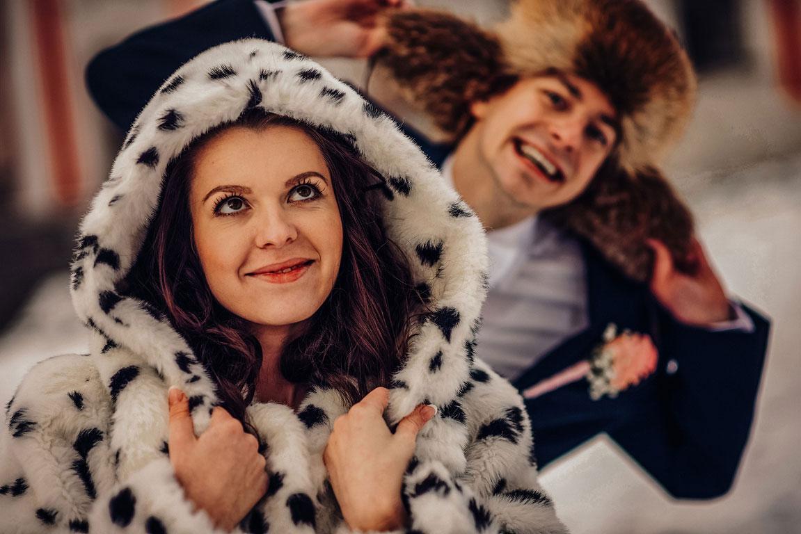 Zimní fotografie ženicha a nevěsty, kteří mají na hlavě kulichy a dělají hlouposti