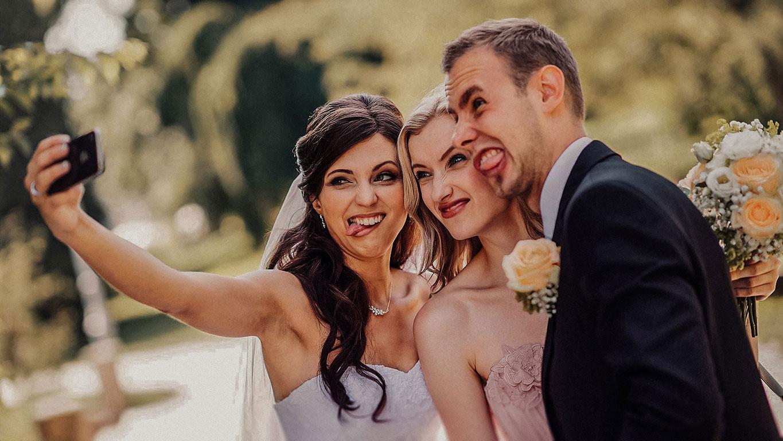 Ženich s nevěstou a družičkou si fotí mobilem selfie a přitom dělají humorné obličeje