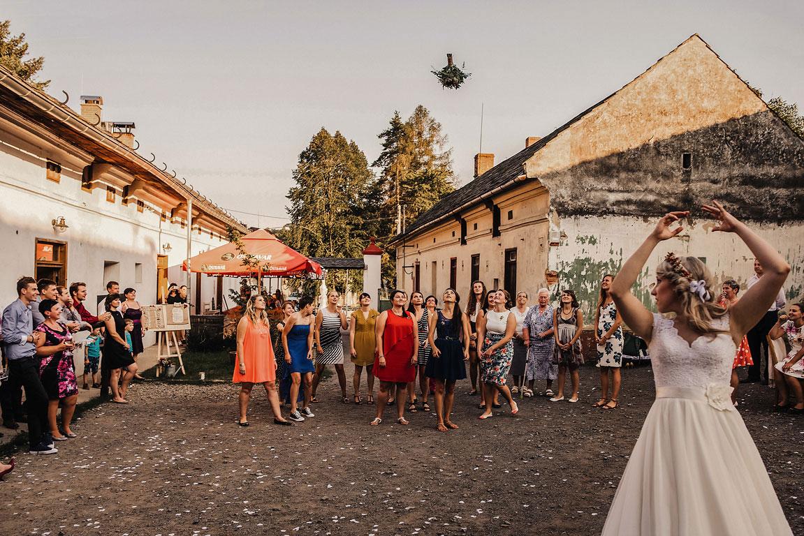 Nevěsta ve Slezském Gruntu za sebe hází svatební kytici a neprovdané ženy ji chytají.