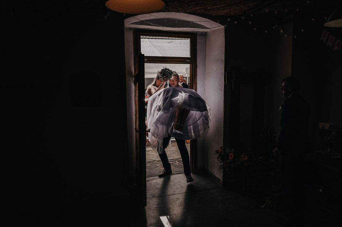 Ženich přenáší přes práh nevěstu, která má v ruce svatební kytici