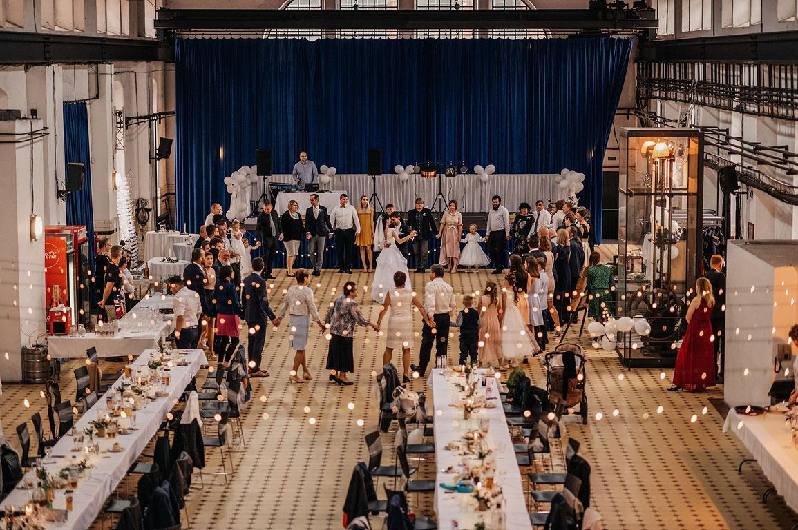 Ženich s nevěstou tančí v kolečku tvořeném svatebčany ve strojovně na dole Landek
