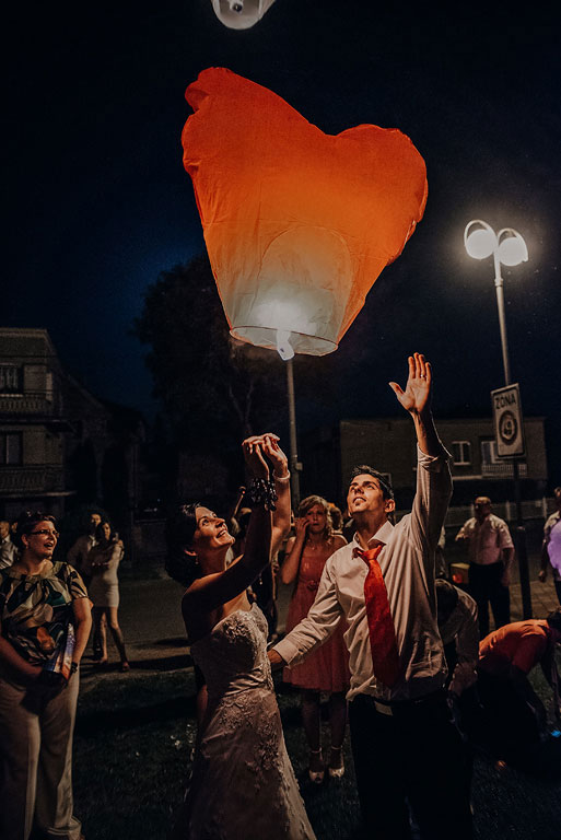 ženich s nevěstou vypouštějí v noci svíticí lampion ve tvaru srdce