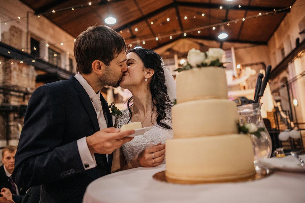Nevěsta s ženichem si dávají polibek a před nimi stojí svatební dort