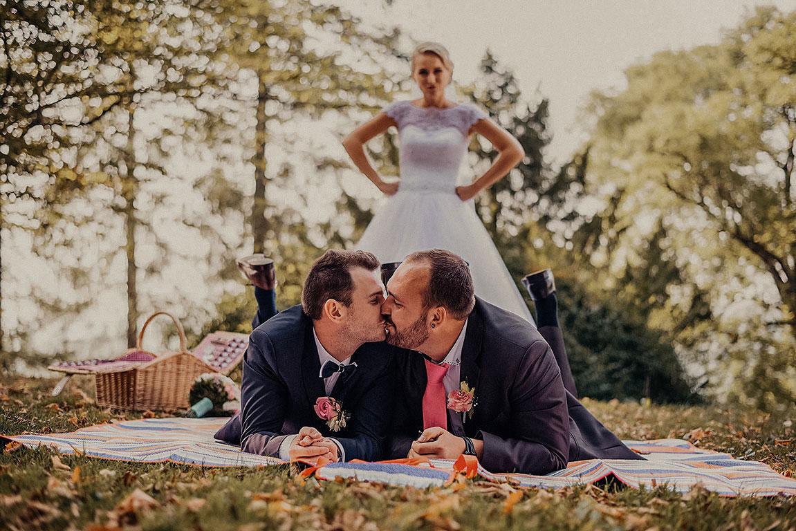 Dva ženichové si dávají polibek na dece v parku. Za nimi stoji rozzlobená nevěsta.
