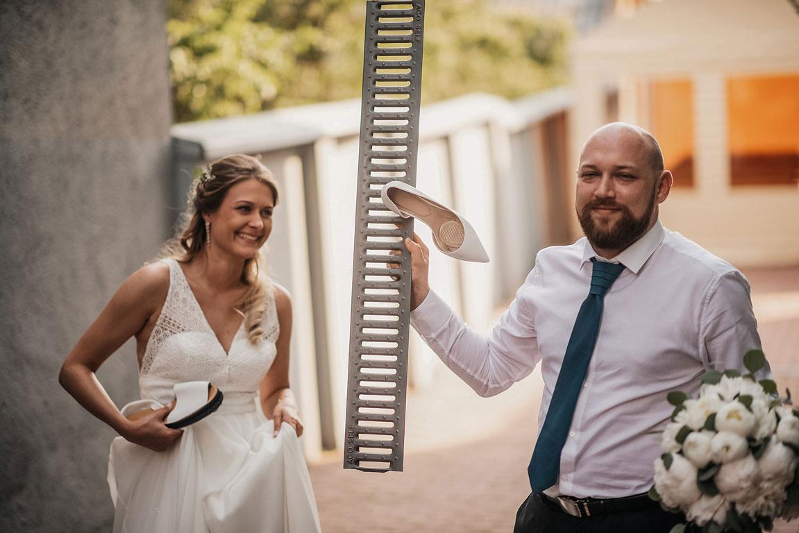 Ženich drží v ruce víko od kanálu, ve kterém je zaseklý střevíc nevěsty. Nevěsta se usmívá.