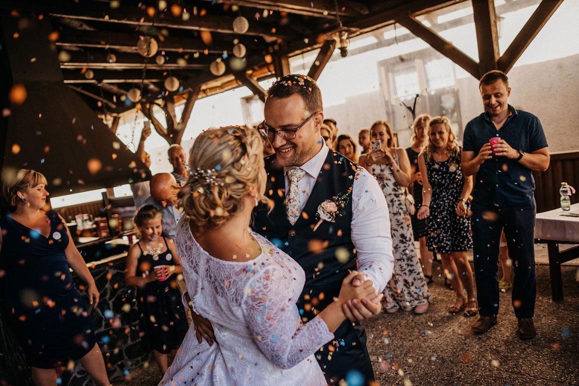 ženich s nevěstou tančí mezi padajícími barevnými konfetami