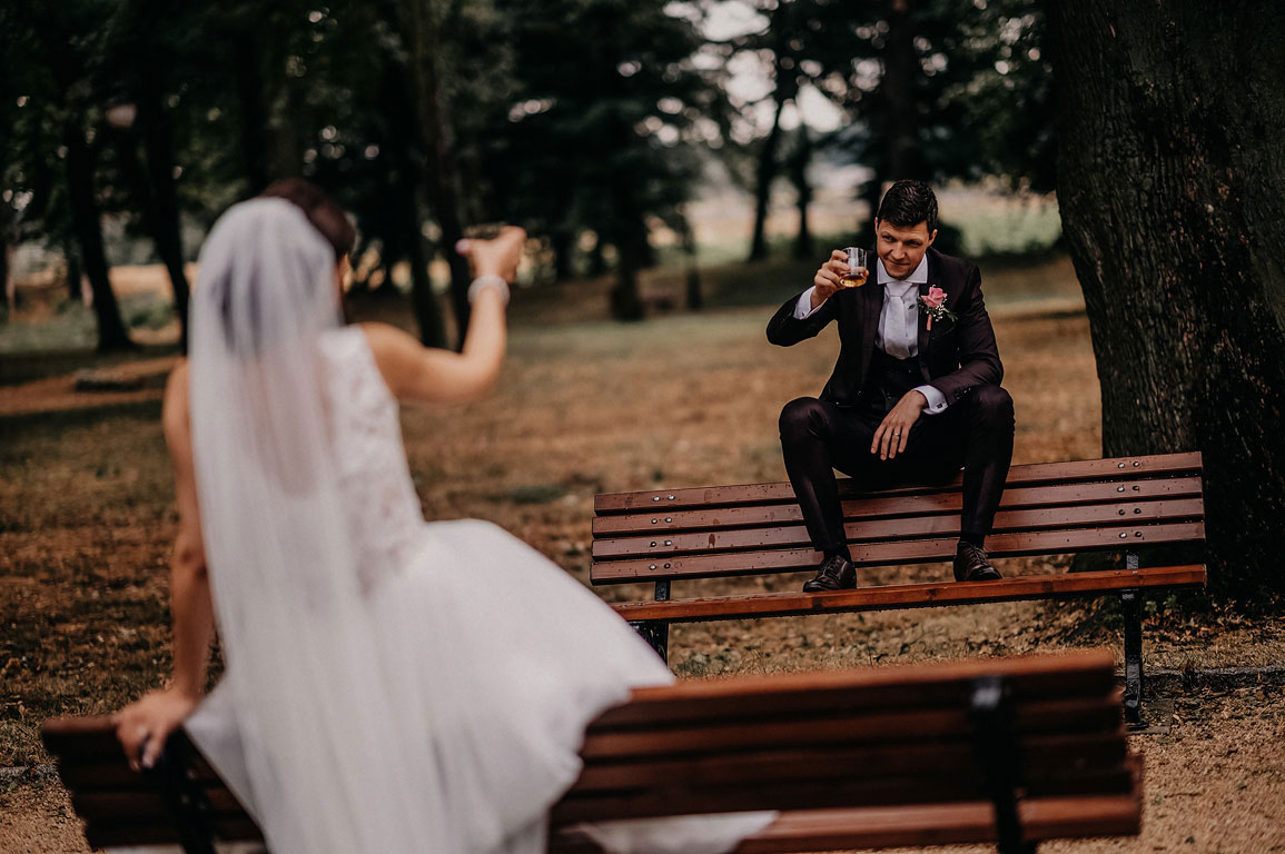 ženich s nevěstou sedí na lavičkách v parku a připíjejí si