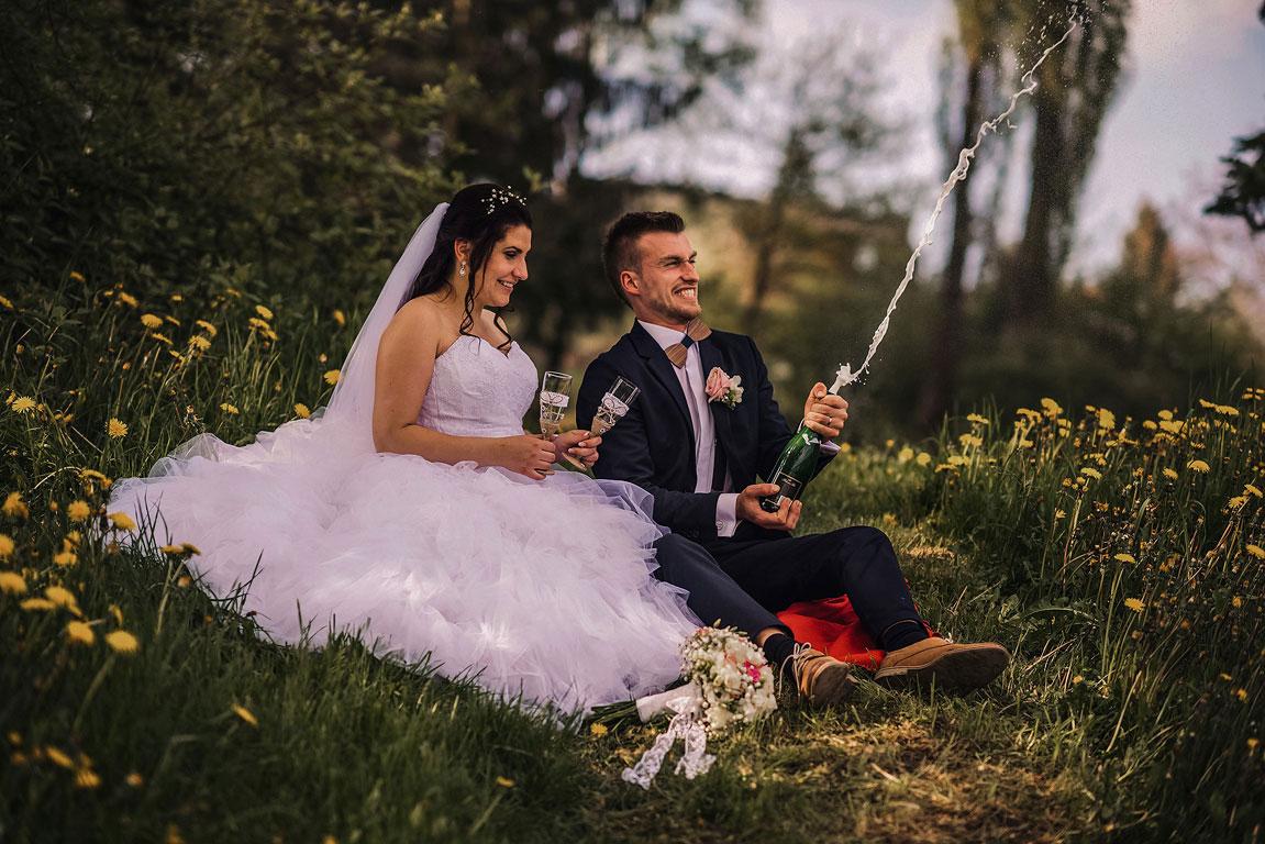 ženich s nevěstou sedí v trávě mezi pampeliškami a otevírají šampaňské, které vystřelilo