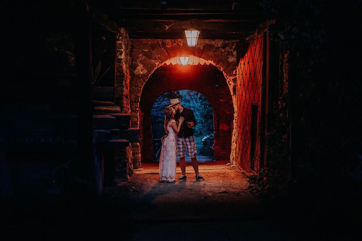 ženich v kraťasech a s pivem v ruce libá nevěstu ve bráně v Novém Hradu u Blanska