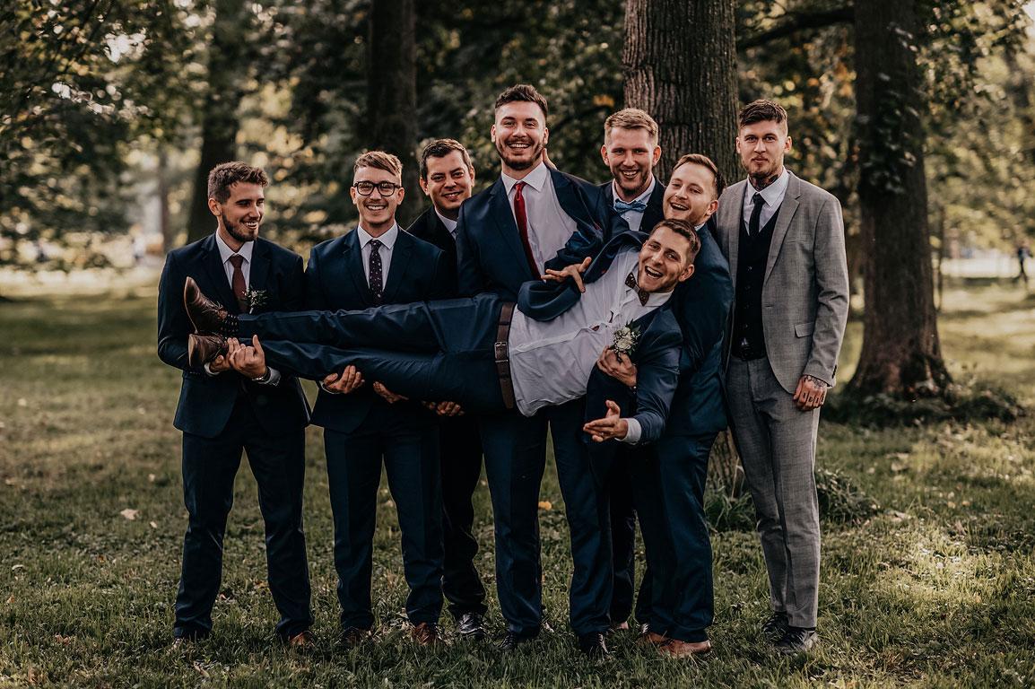 Kamarádi drží v náruči ženicha a všichni se usmívají