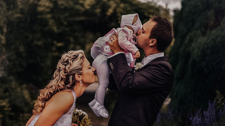 ženich drží miminko a dává mu pusu. Nevěsta čichá k zadku miminka