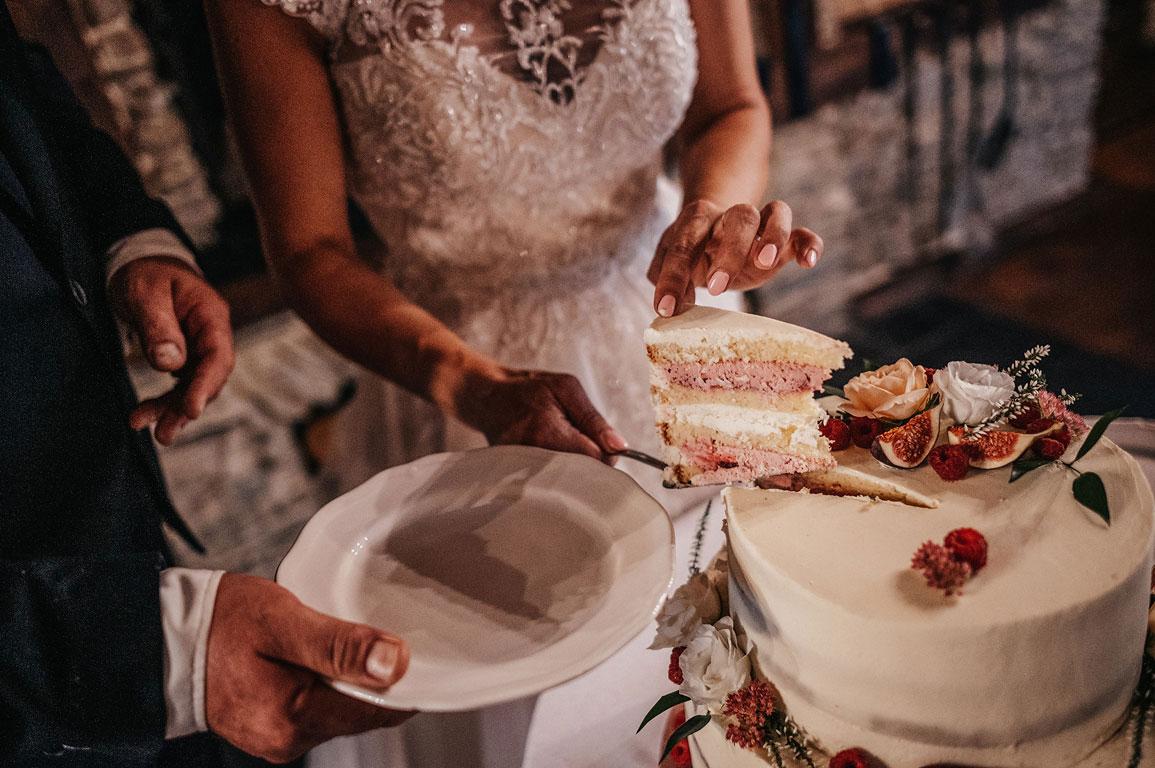 Nevěsta s ženichem nabírají nakrájený dort na talíř