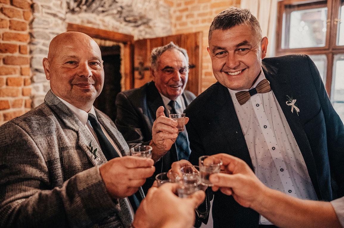 Svatební hosté si připíjejí s fotografem